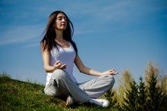 Mooie jonge vrouw die op een flard mediteren van Royalty-vrije Stock Fotografie