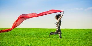 Mooie jonge vrouw die op een groene weide met gekleurd weefsel springen royalty-vrije stock foto