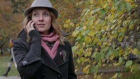 Mooie jonge vrouw die op een mobiele telefoon in een de herfstpark spreken die een hoed dragen Stock Foto's