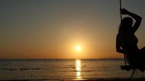 Mooie jonge vrouw die op een schommeling bij gouden zonsondergang door de zon op tropisch strand slingeren Langzame Motie 1920x10 stock videobeelden