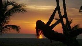 Mooie jonge vrouw die op een schommeling bij verbazende zonsondergang door de zon op tropisch strand slingeren Langzame Motie 192 stock footage