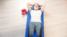 Mooie jonge vrouw die op geschiktheidsmat liggen en abs zitten-UPS doen royalty-vrije stock afbeeldingen