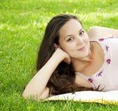 Mooie jonge vrouw die op grasgebied glimlacht Stock Afbeelding