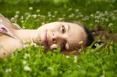Mooie jonge vrouw die op grasgebied glimlacht Royalty-vrije Stock Afbeeldingen