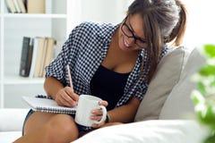 Mooie jonge vrouw die op het notitieboekje schrijven terwijl het drinken van koffie stock afbeelding
