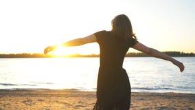 Mooie jonge vrouw die op het strand dansen en op camera in zwarte kleding stellen stock footage