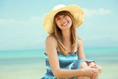 Mooie jonge vrouw die op het strand glimlacht Royalty-vrije Stock Foto's