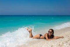 Mooie jonge vrouw die op het strand ligt stock afbeeldingen