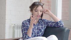 Mooie jonge vrouw die op mobiele telefoon thuis spreken Ontspannen vrouw bij cellphonezitting op laag Meisje die spreken stock videobeelden