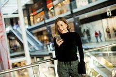 Mooie jonge vrouw die op mobiele telefoon in winkelcentrum kijken stock foto's