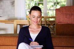 Mooie jonge vrouw die op notastootkussen thuis schrijven Stock Afbeeldingen