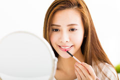 Mooie jonge vrouw die op rode lippenstift zetten Royalty-vrije Stock Afbeelding