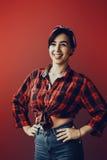 Mooie jonge vrouw die op rood in studio in oude manierkleren wordt geïsoleerd die pinup vertegenwoordigen Stock Foto's
