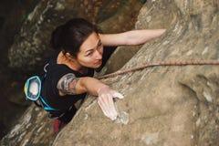 Mooie jonge vrouw die op rots beklimmen stock afbeeldingen