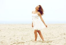 Mooie jonge vrouw die op strand in witte kleding lopen Royalty-vrije Stock Foto