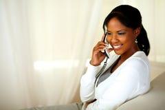 Mooie jonge vrouw die op telefoon glimlacht royalty-vrije stock foto's