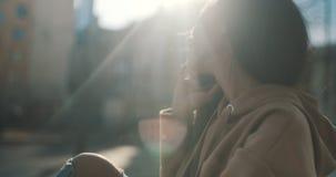 Mooie jonge vrouw die op telefoon tijdens zonnige dag spreken