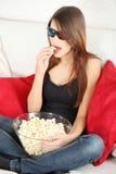 Mooie jonge vrouw die op TV in 3d glazen let Stock Foto