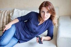 Mooie jonge vrouw die op TV op bank thuis letten stock foto