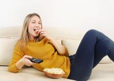 Mooie jonge vrouw die op TV letten en op bank thuis ontspannen Stock Afbeeldingen