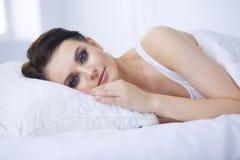 Mooie jonge vrouw die op wit bed liggen Royalty-vrije Stock Afbeeldingen