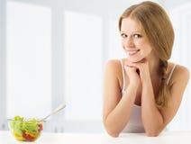 Mooie jonge vrouw die plantaardige salade eet Stock Foto's