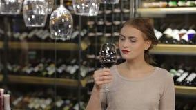 Mooie jonge vrouw die rode wijn proeven stock video