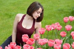 Mooie jonge vrouw die roze tulpentuin bekijken royalty-vrije stock fotografie