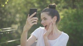 Mooie jonge vrouw die selfie in park nemen stock footage