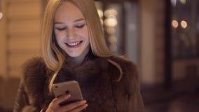 Mooie jonge vrouw die slimme telefoon en het glimlachen gebruiken Het typen bericht, het bekijken mobiel en het glimlachen Het ge stock video