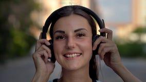 Mooie jonge vrouw die smartphone met behulp van, typend berichten, luisterend aan muziek, het drinken koffie terwijl het lopen op stock foto