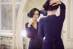 Mooie jonge vrouw die in spiegel binnen kijken stock foto