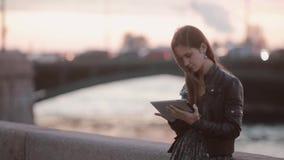 Mooie jonge vrouw die tablet gebruikt Mooie dame die zich bij de kade, het glimlachen bevinden Moderne technologie stock video