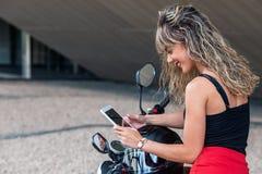 Mooie jonge vrouw die tablet op motorfiets gebruiken royalty-vrije stock afbeelding