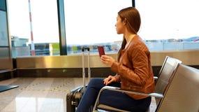 Mooie jonge vrouw die uit venster terwijl het wachten van het inschepen op vliegtuigen met paspoort in haar hand kijken stock foto