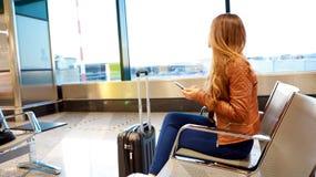 Mooie jonge vrouw die uit venster vliegend vliegtuig bekijken terwijl het wachten van het inschepen op vliegtuigen in luchthavenz royalty-vrije stock afbeelding