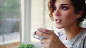 Mooie jonge vrouw die van koffie genieten en zitting glimlachen door het venster in koffie Dame met kop van het stomen van drank stock footage