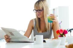 Mooie jonge vrouw die van ontbijt in de keuken genieten Stock Fotografie