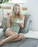 Mooie jonge vrouw die verleidende cake bekijken terwijl binnenshuis het zitten op bank Stock Foto's