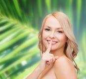 Mooie jonge vrouw die vinger richten aan lippen royalty-vrije stock afbeelding