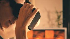 Mooie jonge vrouw die virtuele werkelijkheidsglazen met haar mobiele telefoon gebruiken Betaalbare VR-hoofdtelefoon in actie 4K v stock videobeelden