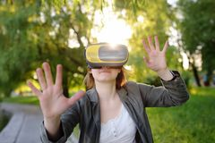 Mooie jonge vrouw die virtuele werkelijkheidshoofdtelefoon met behulp van openlucht VR, VR-glazen, vergrote werkelijkheidservarin stock afbeeldingen