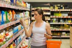 Mooie jonge vrouw die voor graangewas, massa in een kruidenierswinkelsto winkelen Stock Afbeeldingen