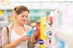 Mooie jonge vrouw die voor schoonheidsmiddelen in een kruidenierswinkelopslag winkelen stock foto's