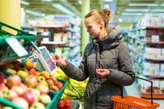 Mooie, jonge vrouw die voor vruchten en groenten in pro winkelen stock fotografie