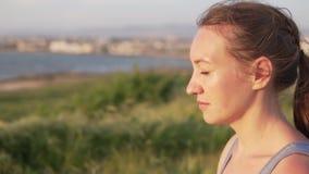 Mooie jonge vrouw die yoga doen door het overzees stock videobeelden