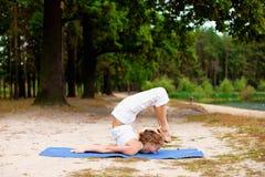 Mooie jonge vrouw die yogaoefening in openlucht doet Royalty-vrije Stock Foto's