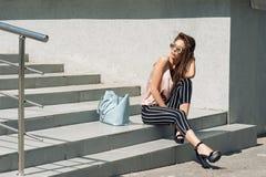 Mooie jonge vrouw die zich bij de ingang aan de ondergrondse garage bevinden Het model draagt modieuze kleren, beige Jersey, en b royalty-vrije stock foto