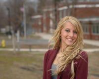 Mooie jonge vrouw die zich buiten een school bevindt Royalty-vrije Stock Afbeeldingen