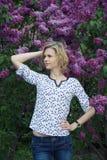Mooie jonge vrouw die zich dichtbij sering bevinden Royalty-vrije Stock Foto